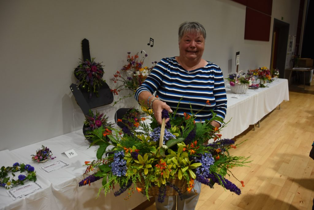 A deserving winner of the Rhoda Henderson Memorial Cup, May Crawford with her wicker basket of cut flowers and behind her, another impressive floral arrangement with the theme Music Festival.