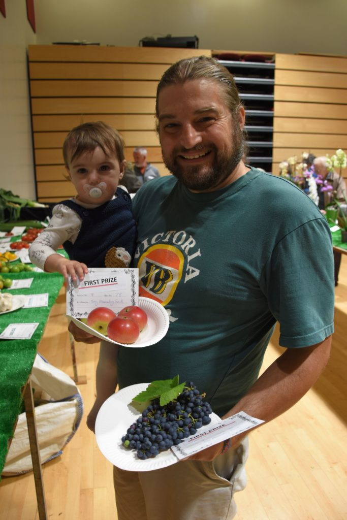 Young Rosalie helps dad Tony Macauley-Smith show off his certificates for his first prize apples and grapes.