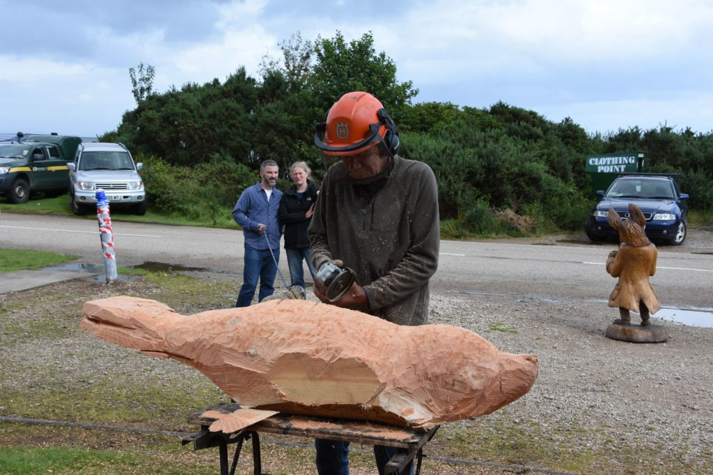 Marvin Elliott 'roughs out' the shape for a dolphin carving.