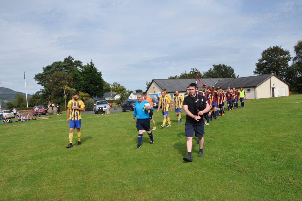 Referee Dougie McInnes leads the teams out with piper Ross Kerr.