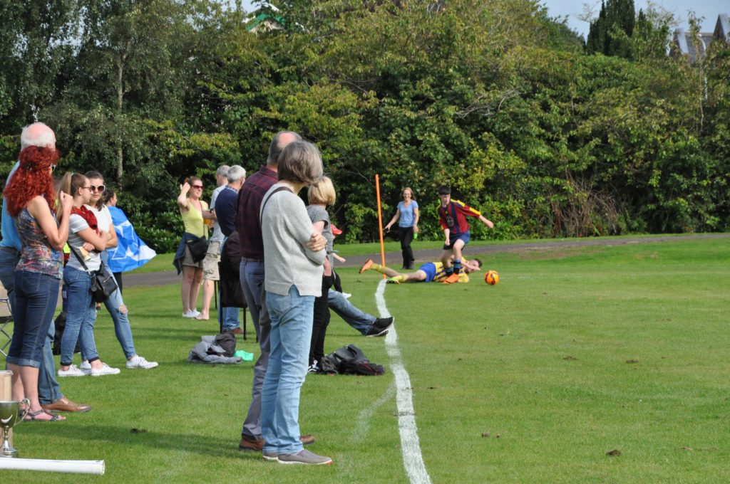 The crowd watch a tussle at the corner flag.