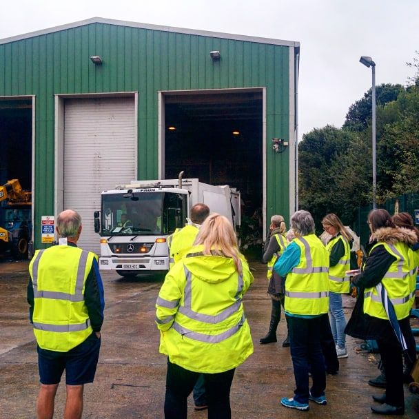 Visitors watch as a refuse collection vehicle unloads its cargo at the processing facility.