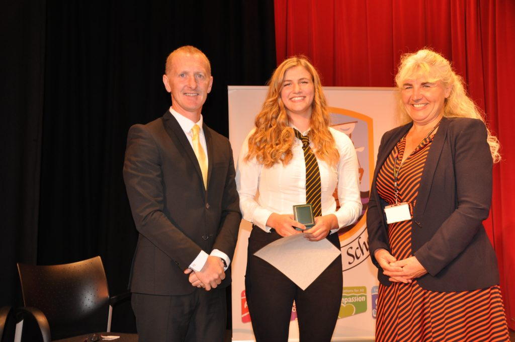 Eilidh Hamill receives the Dux award from head teacher Barry Smith and Laura Cook of North Ayrshire Council.