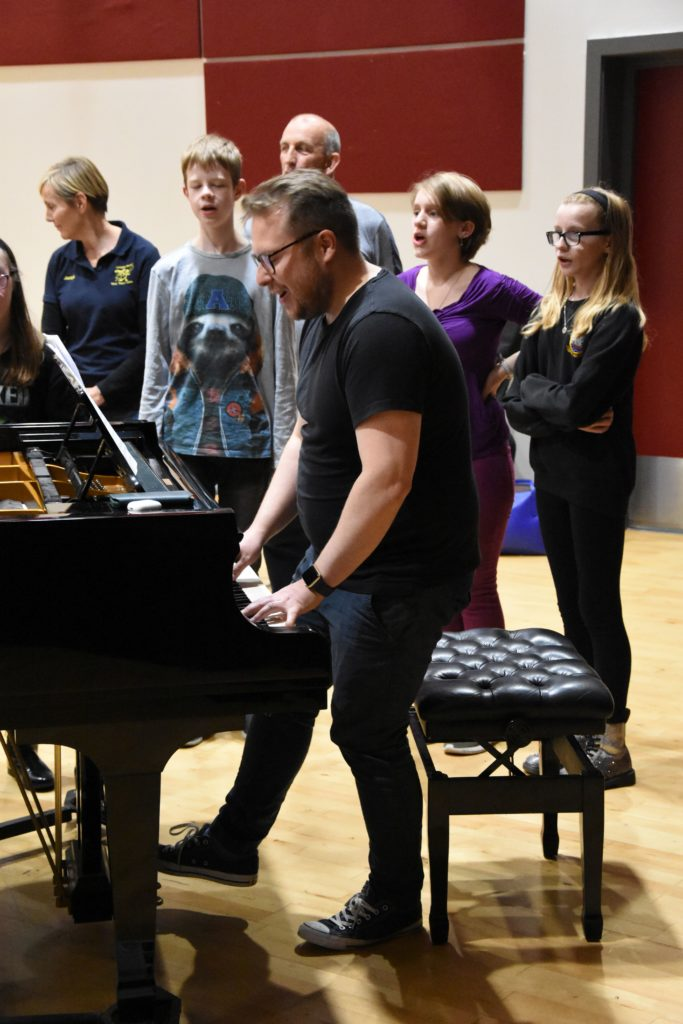 Tutor James O'Neil guides the young singers and plays the piano.
