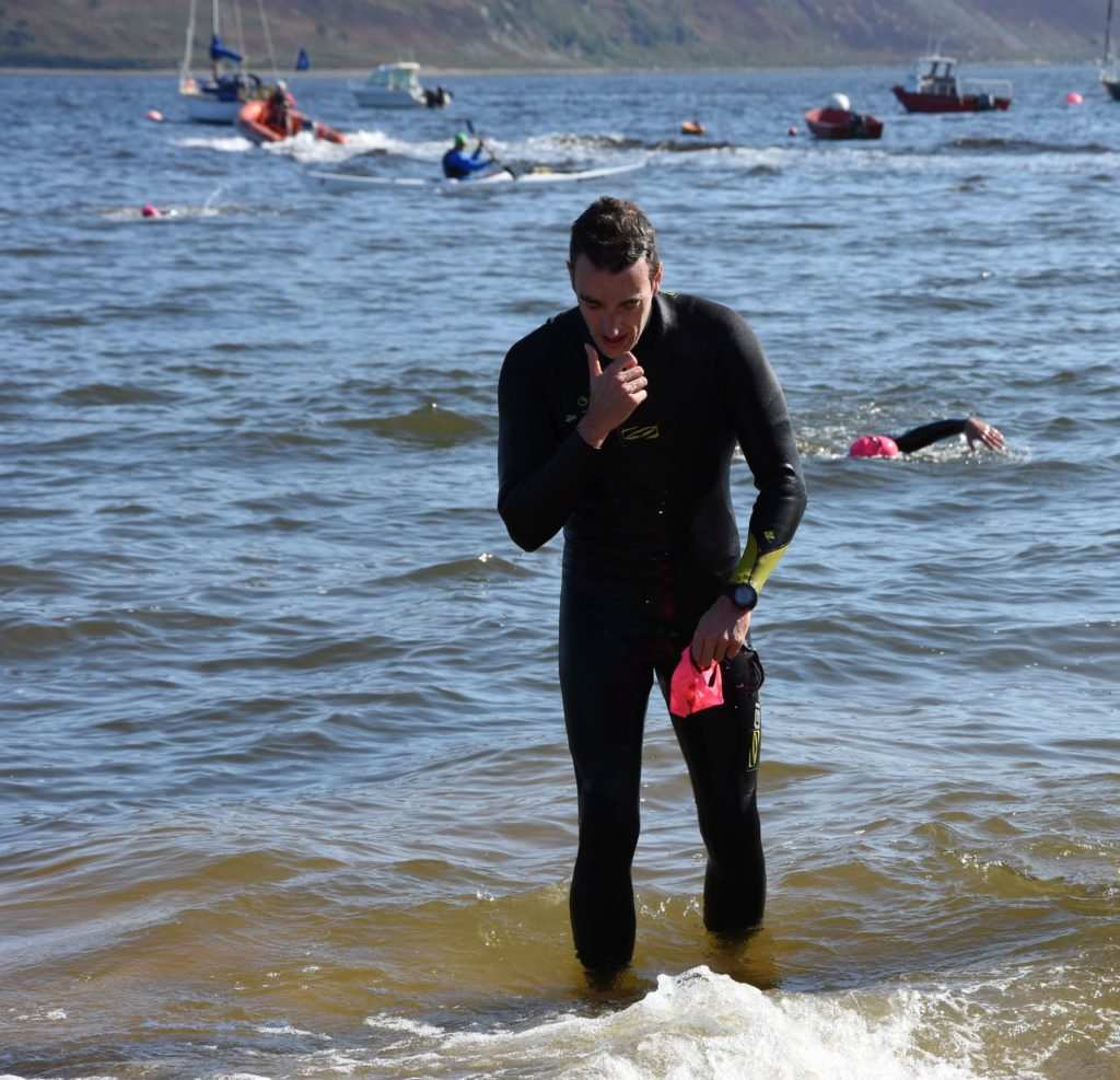 In third place overall and the first local to finish, Glenn Sloss, emerges from the water.