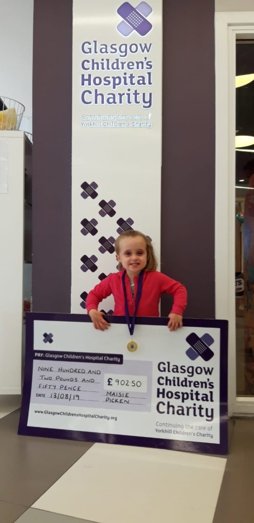 Maisie with the cheque for he £902 of cash donations.