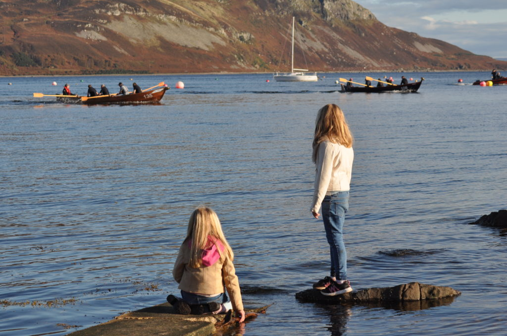 Two young girls watch the action from the seashore.