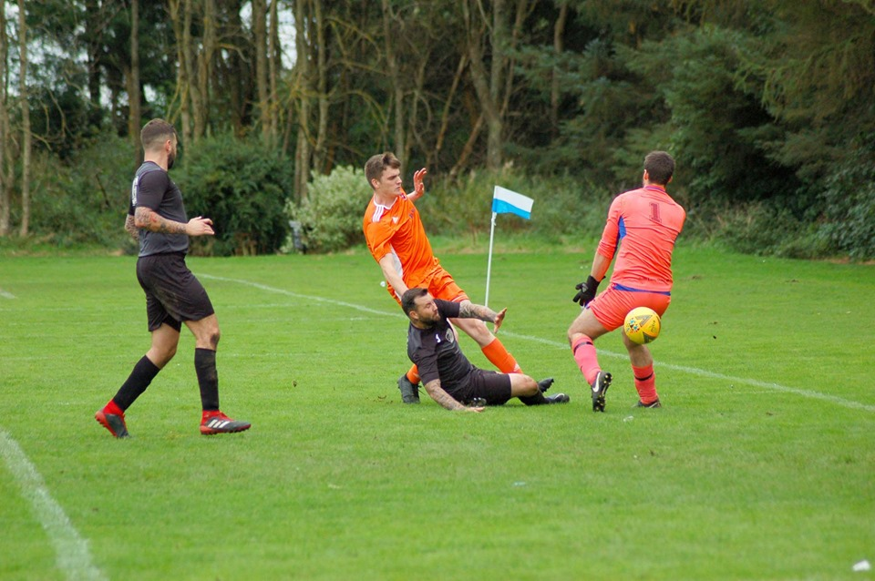 Joel Small kicks the ball past the keeper to score for Arran.