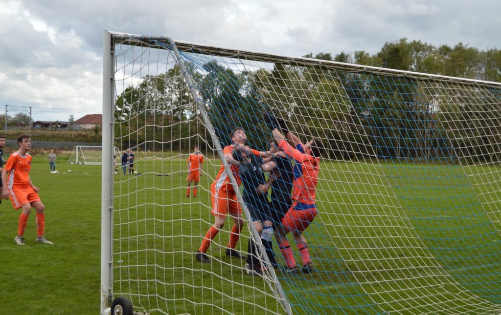 A tense moment in the Irvine goal as players struggle to intercept an overhead ball.