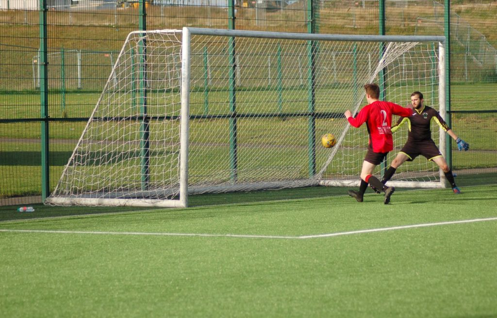 Joel Small drives the ball into the goal with the Eastend keeper powerless to prevent it. No_B43Hfooty03