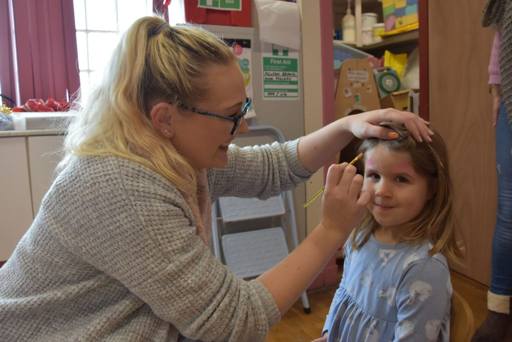 Gemma Bennett transforms a young girl into a unicorn with her face painting.