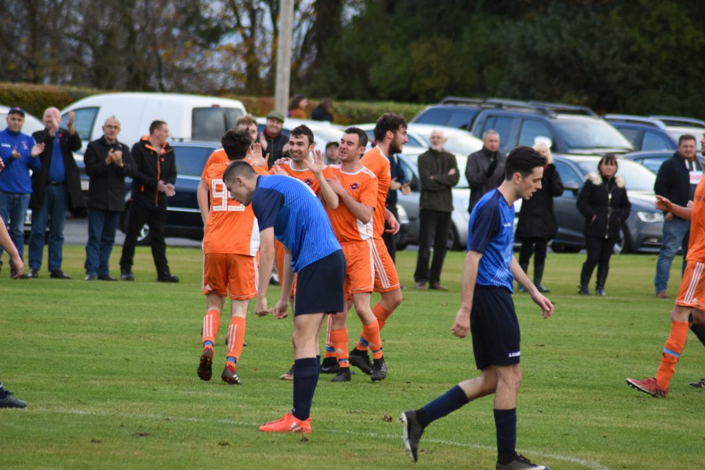 Players congratulate Archie McNicol on his goal while opposition players walk away dejectedly.