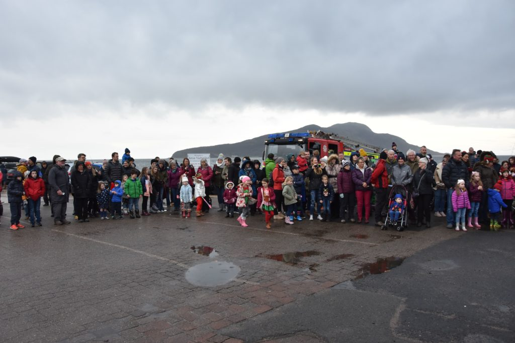 A large crowd of parents and children prepare to join Santa and the procession to the grotto at Lamlash High School.
