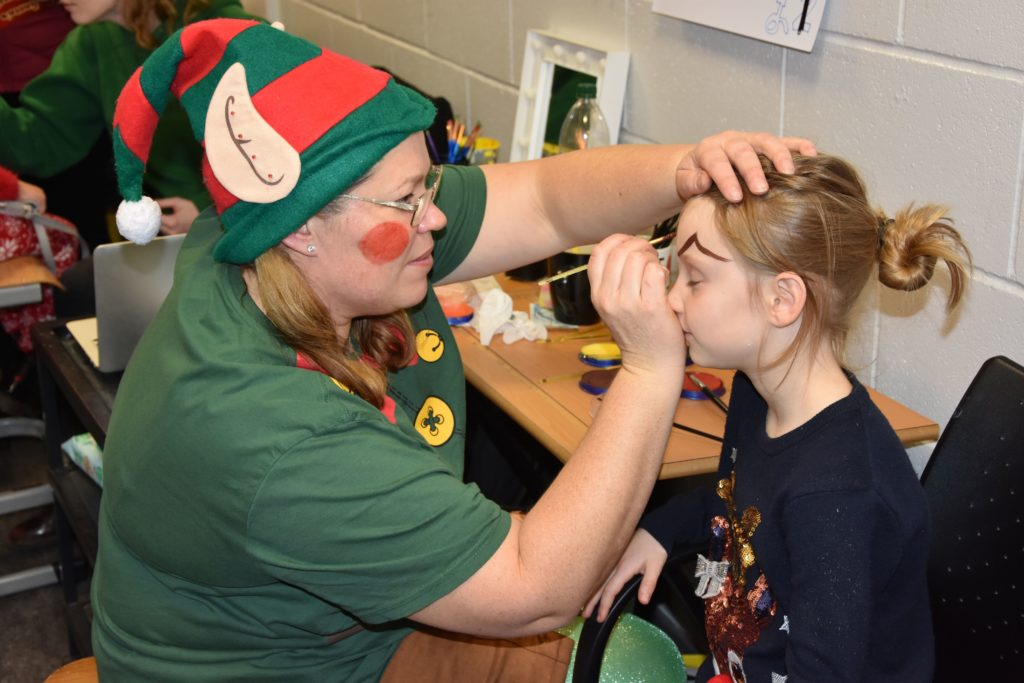 Emma Giering Campbell gets to work painting a young girls face.