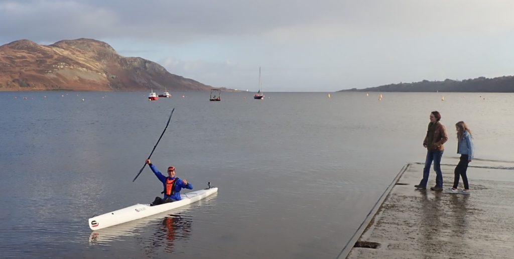 Luke Furze raises his oar triumphantly after making it to the finish line in first position.