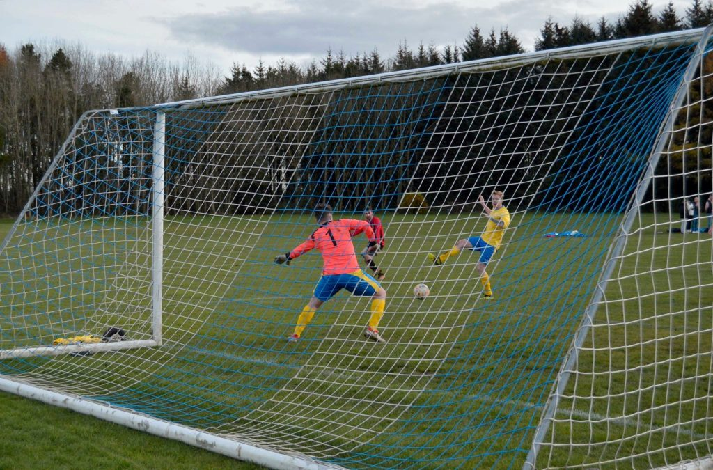 Archie McNicol squeezes the ball between the narrow gap between a Glencairn player and the keeper to score.