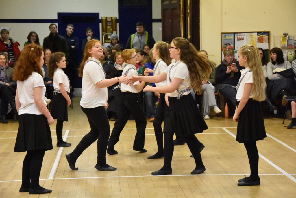 Primary children dance to a Scottish tune